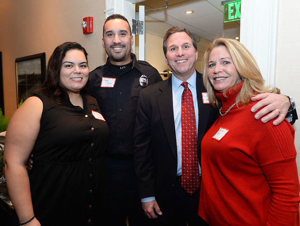 CARL RUSSO/Staff photo. Lawrence police Officer Ivan Soto and his wife Veronica are greeted by Jim and Christine Adams at the Service Club of Andover Night of Giving ceremony. Jim is co-president of the Service Club of Andover. <br /> <br /> This year the Service Club of Andover provided some assistants to Lawrence police Officer Ivan Soto and his wife Veronica because of their hardship during the gas disaster. They were special guest at the Night of Giving. <br /> <br /> Officer Soto became known during the gas disaster when he stayed on duty to help others even after his home exploded and burned during the gas disaster. <br /> <br /> The Service Club of Andover hosted a Night of Giving on December 4th. at  the Andover Inn on the campus of Phillips Academy. The club makes a difference in the community by enriching the lives of our youth and individuals with special needs. <br /> <br /> While  the club sponsors a variety of activities aligned with their mission, The Service Club's principle programs are the High School Mentoring Program, and the Adult Special Needs Program. Both of these programs seek to help individuals achieve their full potential and fulfill needs that would otherwise go unmet. 12/04/2018