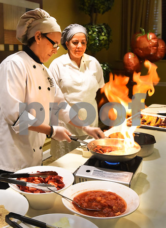 BRYAN EATON/Staff photo. Three liquors go into the glaze of Andover Country Club chef Elaine Chirichiello's strawberry, Mandarin orange and grape tomato sticks along with brown sugar and butter which she's lit on fire with assistant, Lourdes Torres, right.