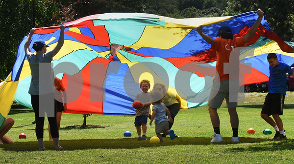 BRYAN EATON/Staff photo. Youngsters run under the parachute to collect ball before the Andover Recreation Department's counselors pull it down.