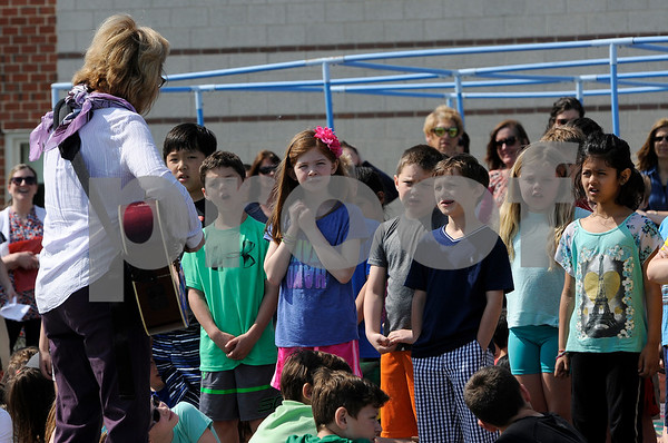 TIM JEAN/Staff photo  Martha Giguere, left, leads second graders as they sing This Land is Your Land, during a ground breaking ceremony at High Plain Elementary/Wood Hill Middle for the accessibility ramp project to the athletic fields.  5/23/18