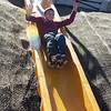 TIM JEAN/Staff photo<br /> <br /> Liam Flanagan, 13, slides down the twelve foot high slide built into the access ramp as town and school officials celebrate the grand opening of the High Plain Elementary and Wood Hill Middle School Athletic Field Accessibility Project. The ramp will connect the schools' basketball court to the lower soccer fields.  10/5/18