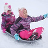 MIKE SPRINGER/Staff photo<br /> Mamie Zhou, left, her friend Mia Zhao, both 7, sled down the hill together Monday at Andover High School.<br /> 12/2/2019