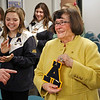MIKE SPRINGER/Staff photo<br /> Retiring Andover High School girls swimming and diving head coach Mariln Fitzgerald holds up the varsity letter she recieved during the Andover School Committee meeting Thursday night. applauding at left is 2018 team co-captain Riley Spring. Behind her are teammates Rebecca Page, left, and Samira Sayan. During her career as coach, Andover won 18 out of the last 19 state championships, including 2018.<br /> 1/10/2019