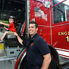 CARL RUSSO/Staff photo. Andover firefighter Jonathan Booth watches as Anthony Vinson-Ventola. 4, plays behind the wheel of fire engine 1. Firefighter Booth has been a firefighter just over a year.<br /> <br /> The Friends of the Andover Memorial Hall Library and the town's fire, police and DPW  departments sponsored the annual vehicle night on Tuesday (7/16). The library parking lot was converted into a display of large DPW and fire trucks and a variety of police vehicles for kids to view, climb inside and sit behind the wheel. Gifts were given out to the kids by the Library, police and fire departments. 7/16/2019