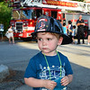 CARL RUSSO/Staff photo. Homer Colwell, 2 is ready to be a firefighter for the night. <br /> <br /> The Friends of the Andover Memorial Hall Library and the town's fire, police and DPW  departments sponsored the annual vehicle night on Tuesday (7/16). The library parking lot was converted into a display of large DPW and fire trucks and a variety of police vehicles for kids to view, climb inside and sit behind the wheel. Gifts were given out to the kids by the Library, police and fire departments. 7/16/2019