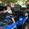 CARL RUSSO/Staff photo. Austin Gibson, 3 sits behind the wheel of an ATV, All Terrain Vehicle with Andover police officer Glen Ota looking on. Officer Ota has been on the police force for 24 years. <br /> <br /> The Friends of the Andover Memorial Hall Library and the town's fire, police and DPW  departments sponsored the annual vehicle night on Tuesday (7/16). The library parking lot was converted into a display of large DPW and fire trucks and a variety of police vehicles for kids to view, climb inside and sit behind the wheel. Gifts were given out to the kids by the Library, police and fire departments. 7/16/2019