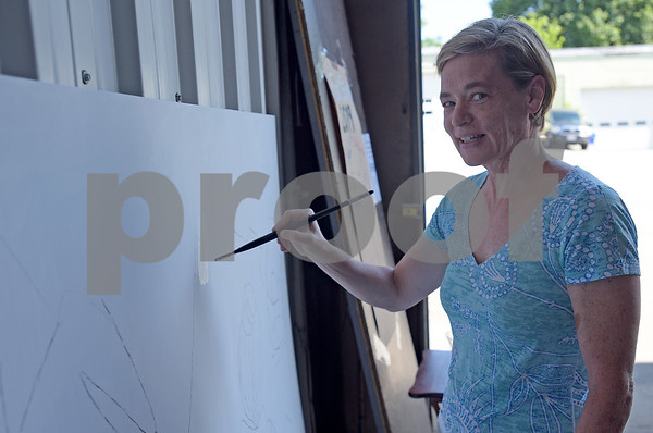 """TIM JEAN/Staff photo<br /> <br /> Select Board member Annie Gilbert paints a small section of a new mural at the former town yard. Tuesday town officials unveiled the outline of the mural and start painting, which is themed """"Welcome to Andover.""""    7/2/19"""