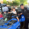 CARL RUSSO/Staff photo. Austin Gibson, 3 sits behind the wheel of an ATV, All Terrain Vehicle with Andover police officer Glen Ota assisting. Officer Ota has been on the police force for 24 years. <br /> <br /> The Friends of the Andover Memorial Hall Library and the town's fire, police and DPW  departments sponsored the annual vehicle night on Tuesday (7/16). The library parking lot was converted into a display of large DPW and fire trucks and a variety of police vehicles for kids to view, climb inside and sit behind the wheel. Gifts were given out to the kids by the Library, police and fire departments. 7/16/2019