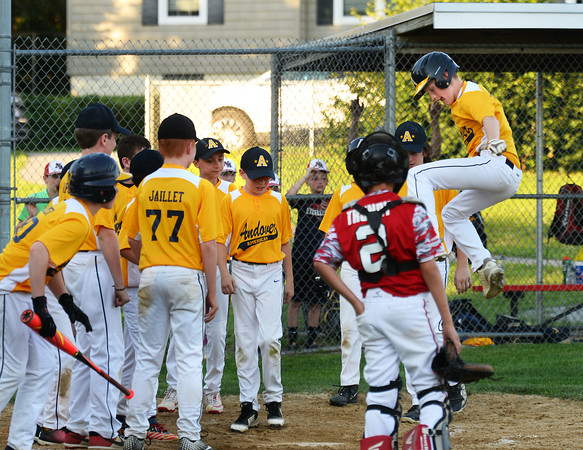 CARL RUSSO/Staff photo Andover American Chris Jaillet leaps into the air and lands on home plate before celebrating his home run with his teammates. <br /> <br /> North Andover defeated Andover American 9-8 in Little League baseball action at the Carl Thomas field in North Andover Friday night.  6/28/2019