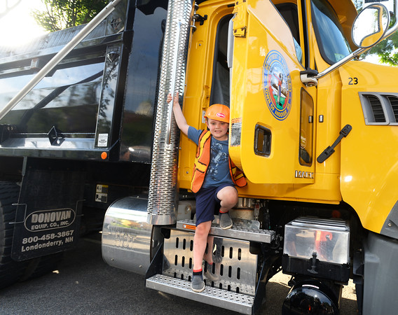 CARL RUSSO/Staff photo. Dressed for the occasion,  Mason Richards, 5 of Andover climbs out of large DPW dump truck. <br /> <br /> The Friends of the Andover Memorial Hall Library and the town's fire, police and DPW  departments sponsored the annual vehicle night on Tuesday (7/16). The library parking lot was converted into a display of large DPW and fire trucks and a variety of police vehicles for kids to view, climb inside and sit behind the wheel. Gifts were given out to the kids by the Library, police and fire departments. 7/16/2019