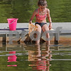 MIKE SPRINGER/Staff photo<br /> Nine-year-old Mina Tamas of Andover looks into the water while holding still and preparing to use a net to catch sunfish on Sunday at Pomps Pond in Andover. Using bread for bait, Mina was able to catch and release more fish than she could count.<br /> 6/9/2019