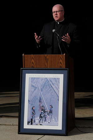 TIM JEAN/Staff photo<br /> <br /> Reverend Paul O'Brien of St. Patrick Church speaks at the podium during the annual 9/11 memorial ceremony at the Ladder 4 Fire Station in Lawrence.   9/11/19