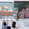 MIKE SPRINGER/Staff photo<br /> Ice cream truck volunteers Sophie Diamantis, 7, and Anthony Archambault, 11, both of Andover, listen as a young customer places an order during the annual Greek Festival on Sunday at Sts. Constantine and Helen Greek Orthodox Church in Andover. <br /> 9/8/2019