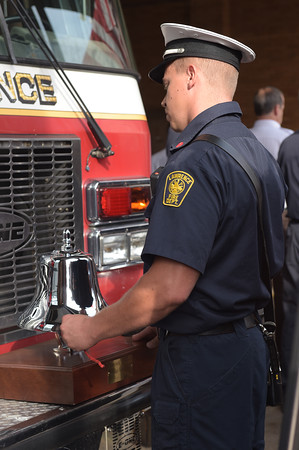 """TIM JEAN/Staff photo<br /> <br /> Lawrence Fire Lt. Corey Scott strikes a """"5-5-5-5"""" alarm on a bell to remember those who died in the line of duty during the annual 9/11 memorial ceremony at the Ladder 4 Fire Station in Lawrence.   9/11/19"""