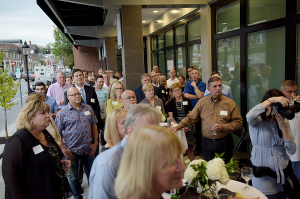 TIM JEAN/Staff photo<br /> <br /> A large crowd listens to Paul Kneeland, co-developer of the redevelopment project as he welcomes friends, town officials, and business owners during a ribbon cutting ceremony for the Draper Block, in downtown Andover.   9/26/19