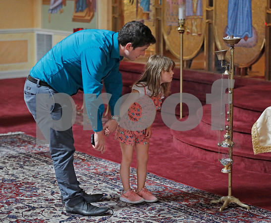 MIKE SPRINGER/Staff photo<br /> Lambi Nash of Peabody holds his five-year-old daughter Azaliea's hand as she investigates the incense at Sts. Constantine and Helen Greek Orthodox Church during the 2019 Greek Festival on Sunday in Andover. <br /> 9/8/2019
