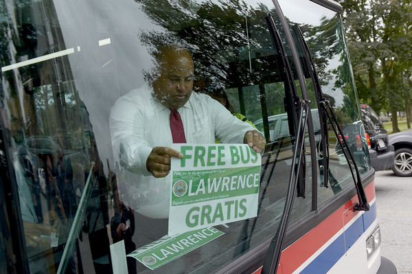 TIM JEAN/Staff photo<br /> <br /> Lawrence Mayor Daniel Rivera attaches a free bus sign to the front window of the bus to promote that its free. The City of Lawrence is paying the MVRTA to run three free bus routes within the city, for the next two years.    9/10/19