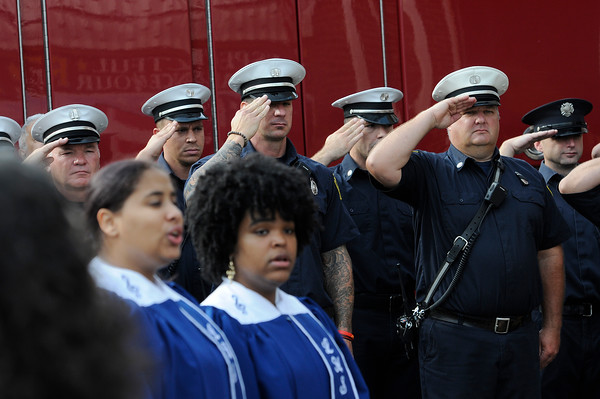 TIM JEAN/Staff photo<br /> <br /> Lawrence Firefighters salute while the Lawrence High School ensemble sing during the annual 9/11 memorial ceremony at the Ladder 4 Fire Station in Lawrence.   9/11/19