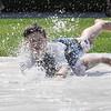 TIM JEAN/Staff photo<br /> <br /> After biking around town Matthew Raymond cools off on the slip N slide behind the Cormier Youth Center. The center has reopened but many activities are in small groups outside doing actives like hiking, biking, and kayaking.    7/29/20