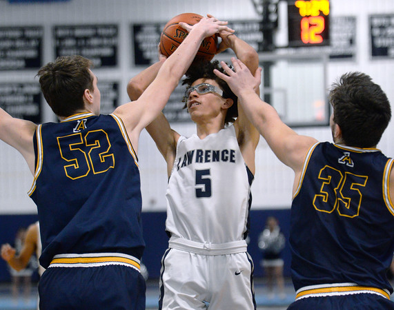 CARL RUSSO/Staff Photo. Lawrence's Jeremiah Melendez takes the jump shot over Andover's Aidan Cammann, left and captain Michael Slayton. Lawrence defeated Andover 60-54 in boys Basketball action in the D1 North tournament. 2/25/2020