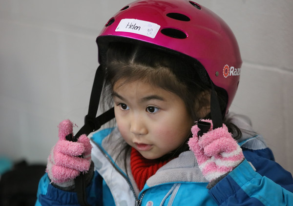 """MIKE SPRINGER/Staff photo<br /> Helen Yu fastens her helmet in preparation for an """"It's Great to Skate"""" ice skating clinic Monday at Phillips Academy in Andover.<br /> 2/17/2020"""