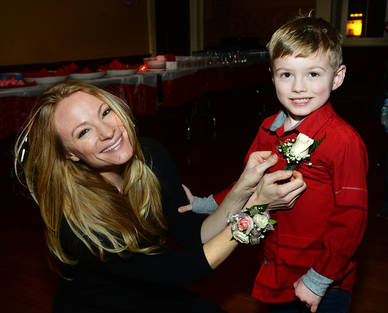 CARL RUSSO/Staff photo Rebecca Lackey pins a flower on her son, Spencer  age 4. The annual Valentine's Dance sponsored by Andover's Department of Recreation was held Friday night at the Town House (Old Town Hall) <br /> <br /> The event is held for boys ages 4-10 for moms to celebrate Valentine's Day with the special little guy in their life. <br /> <br /> An evening of dance with music provided by Ted Entertainment DJ, Ted Teichert of Andover was provided along with games, prizes, and refreshments. 2/7/2020.