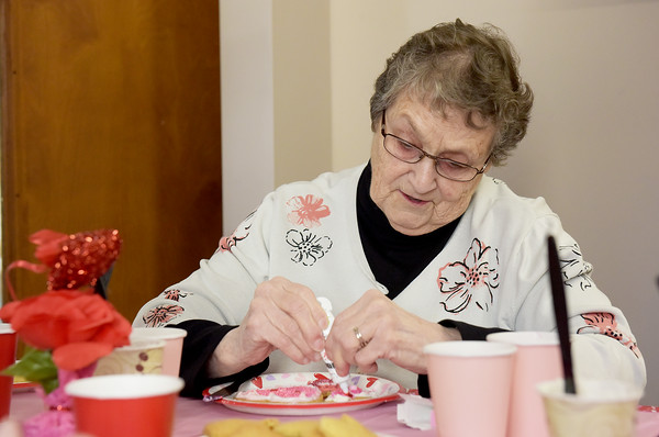 TIM JEAN/Staff photo <br /> <br /> Marilyn Nolan, a front desk volunteer enjoys decorating a Valentine's Day cookie at the Andover Senior Center. The center is temporary in the basement of the Ballardvale Church on Clark Road. 2/12/20