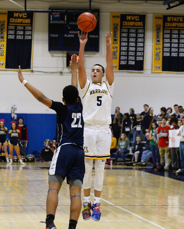 CARL RUSSO/Staff photo Andover captain, Kyle Rocker takes the three point jump short over Lawrence captain, Noah Tejada. Andover defeated Lawrence 66-57 in boys basketball action Friday night. 2/14/2020.