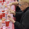 TIM JEAN/Staff photo <br /> <br /> Joan Fox, board member of the council on aging decorates a Valentine's Day cookie at the Andover Senior Center. The center is temporary in the basement of the Ballardvale Church on Clark Road. 2/12/20
