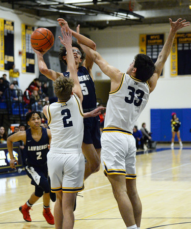 CARL RUSSO/Staff photo Andover's Ryan MacLellan, left and Ryan Grecco double team to stop Lawrence's Jeremiah Melendez drive to the basket. Andover defeated Lawrence 66-57 in boys basketball action Friday night. 2/14/2020.