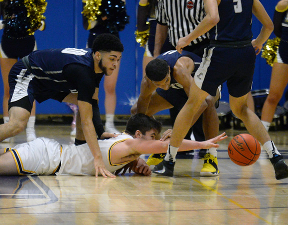 CARL RUSSO/Staff photo Andover captain Michael Slayton dives for the loose ball along with Lawrence captains Angel Herrera, left and Brandon Goris.  Andover defeated Lawrence 66-57 in boys basketball action Friday night. 2/14/2020.
