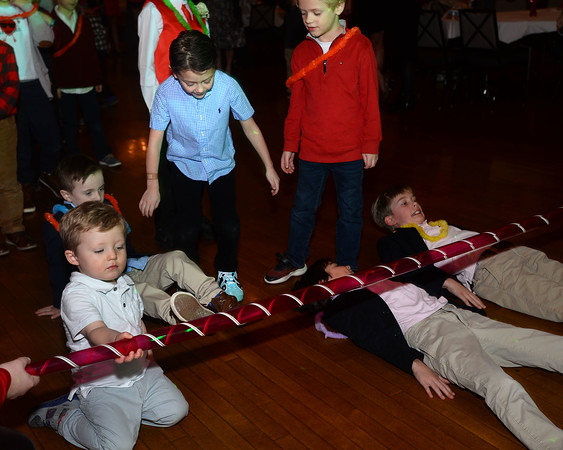 CARL RUSSO/Staff photo Luke O'Brien, 2, left helps with holding the limbo stick as the boys go how low can you go. The annual Valentine's Dance sponsored by Andover's Department of Recreation was held Friday night at the Town House (Old Town Hall) <br /> <br /> The event is held for boys ages 4-10 for moms to celebrate Valentine's Day with the special little guy in their life. <br /> <br /> An evening of dance with music provided by Ted Entertainment DJ, Ted Teichert of Andover was provided along with games, prizes, and refreshments. 2/7/2020.