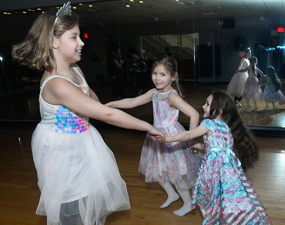 CARL RUSSO/Staff photo. From left, Annabelle Groff, 9 of Andover dances with her sister Chloe, 5 and Isabella Melanson, 5 of North Andover. The Andover/North Andover YMCA held a family dance party Friday night. Around 25 boys and girls and parents enjoyed pizza, music and fun.2/21/2020.