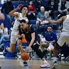 CARL RUSSO/Staff Photo. Andover's captain Kyle Rocker has trouble weaving around Lawrence's Jeremiah Melendez, left and captain Brandon Goris. Lawrence defeated Andover 60-54 in boys Basketball action in the D1 North tournament. 2/25/2020.