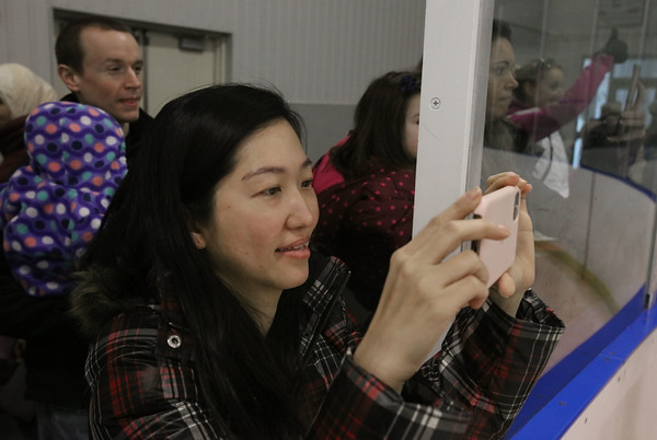 MIKE SPRINGER/Staff photo<br /> Venus Takkarnpanit photographs her child during an ice skating clinic Monday at Phillips Academy in Andover.<br /> 2/17/2020