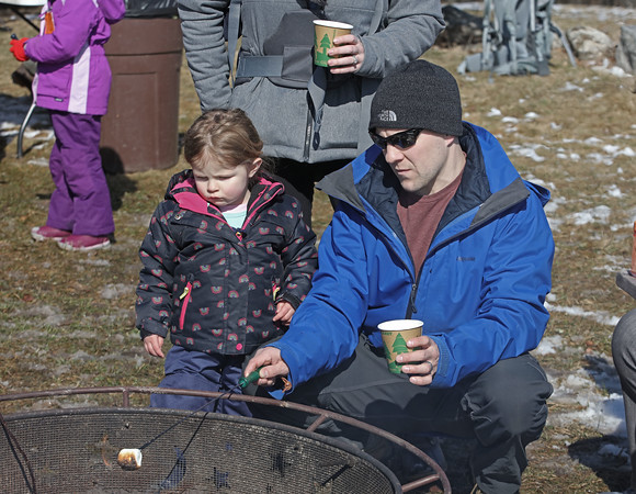 MIKE SPRINGER/Staff photo<br /> Ryan Olivastri of Andover roasts a marshmallow with his daughter Emma, 3, during the Winter Fun Day on Feb. 17 at the Ward Reservation in Andover.<br /> 2/17/2020