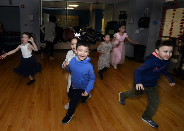 CARL RUSSO/Staff photo. Bobur Nabiev, far right, 8 of Andover leads other children as they make up their own games and do less dancing.The Andover/North Andover YMCA held a family dance party Friday night. Around 25 boys and girls and parents enjoyed pizza, music and fun.2/21/2020.