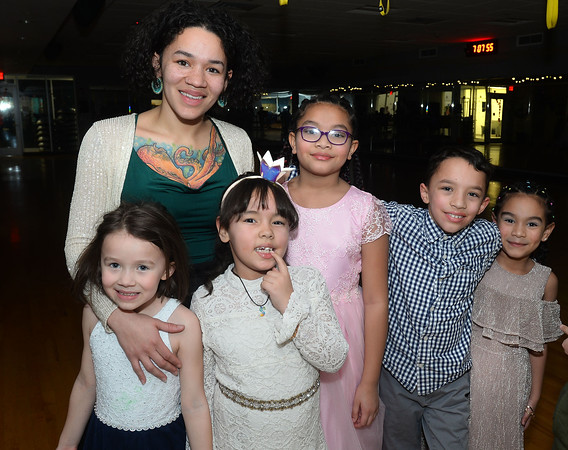 CARL RUSSO/Staff photo. Denia Taylor of Andover and her family, from left, her daughter, Cat Taylor, 7; nieces Sophia Rodriguez, 7 and Alleena Rios, 8; her son, Max Taylor, 8 and niece, Lizzie Rios, 6 make it a true family dance party. The Andover/North Andover YMCA held a family dance party Friday night. Around 25 boys and girls and parents enjoyed pizza, music and fun.2/21/2020.