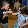 CARL RUSSO/Staff photo. Jesus Rosa, 5 of Lawrence is curious of the aroma of Isabella Melanson's  wrist corsage, She is 5 and lives in North Andover. The Andover<br /> /North Andover YMCA held a family dance party Friday night. Around 25 boys and girls and parents enjoyed pizza, music and fun.2/21/2020.