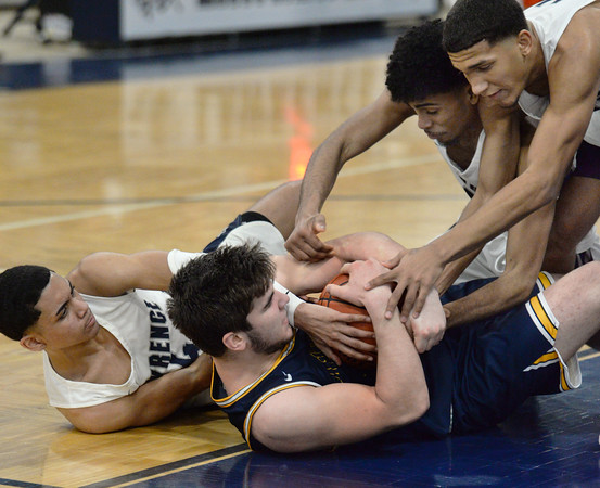 CARL RUSSO/Staff Photo. Andover's captain, Michael Slayton fights for the loose ball with Lawrence's Cristian Moscat, left, Gabriel Zorrilla and captain Brandon Goris, right. Lawrence defeated Andover 60-54 in boys Basketball action in the D1 North tournament. 2/25/2020.