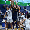 CARL RUSSO/Staff photo. Andover captain, Kyle Rocker is fouled driving to the basket against Lawrence captain, Brandon Goris, left and Carlos Pabon. <br /> <br /> Lawrence defeated Andover 67-63 in boys' basketball action Tuesday night. 1/14/2020