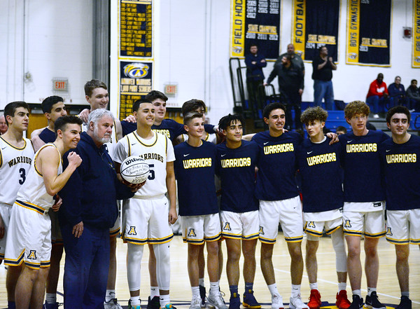 CARL RUSSO/Staff photo Surrounded by his Warrior teammates, Kyle Rocker was presented a souvenir ball honoring him for scoring his 1,000 plus career points during the game at Methuen high on January 24. The ball was presented during Andover's next home game on January 28.  1/28/2020
