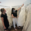 TIM JEAN/Staff photo<br /> <br /> Bridal intern stylists Audrey Tobin, left, and Sabrina Hogan pick out wedding gowns for brides to try on at Brides Across America in Andover. The non-profit who has been giving away free wedding gowns to military personal for several years, is now giving free gowns to COVID-19 front line healthcare workers and first responders.  7/3/20