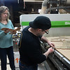 CARL RUSSO/Staff photo. After the plastic is cut to size, Deanna and Stewart Junge demonstrate how the paper is removed. The item is usually shipped to the customer with the paper attached to protect the clear plastic. <br /> <br /> Deanna and Stewart Junge have own Landmark Finish for 20 years, a cabinetry business in Andover. But now they make plastic barriers to put between work stations in offices or to protect employees from the public in the age of coronavirus.  4/30/2020
