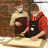 TIM JEAN/Staff photo<br /> <br /> Colby Junge, 11, left, who parents own Landmark Finish in Andover, explains to Jack Buelow, 11, from the North Andover Youth Center how to use an orbital sander during a woodworking class. Landmark Finish have started a partnership with the North Andover Youth Center to provide a learning woodworking experience for kids from the center.  2/3/21