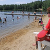 TIM JEAN/Staff photo<br /> <br /> Lifeguard Steven Parrill, 20, of Andover watches over the swimmers at Andover's Pomps Pond. The pond is officially open for the season with restrictions because of the coronavirus.  7/2/20