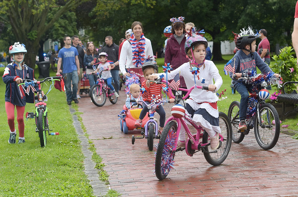 TIM JEAN/Staff photo<br /> <br /> Sloan Sutton, 5, left, of Andover, and her brother Miles, 8, decorated their bicycles with red, white and blue as they peddle through the Park during the annual July 4th Horribles Parade in Andover. The route was changed this year and started in front of Town Hall on Bartlett St., right onto Chestnut, then right on to Whittier Court and then into the park where it ended.   7/4/21