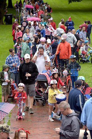 TIM JEAN/Staff photo<br /> <br /> Children and their parents decorated with red, white and blue walk through the Park during the annual July 4th Horribles Parade in Andover. The route was changed this year and started in front of Town Hall on Bartlett St., right onto Chestnut, then right on to Whittier Court and then into the park where it ended.   7/4/21