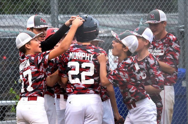 TIM JEAN/Staff photo<br /> <br /> North Andover's Danny Murphy is swarmed by his teammates after hitting a home run against Andover in District 14 Little League Championship title game on Tuesday evening.     7/13/21