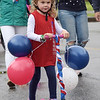 TIM JEAN/Staff photo<br /> <br /> Etta Rogers, 4, of Andover, pushes her scooter decorated with red, white and blue balloons for the annual July 4th Horribles Parade in Andover. The route was changed this year and started in front of Town Hall on Bartlett St., right onto Chestnut, then right on to Whittier Court and then into the park where it ended.   7/4/21